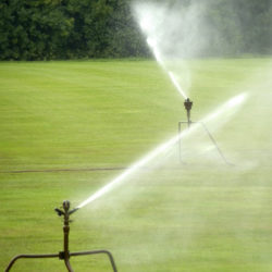 A telephoto lens captured this shop of two sprinklers in action. There is space on the sides for text or additional images.